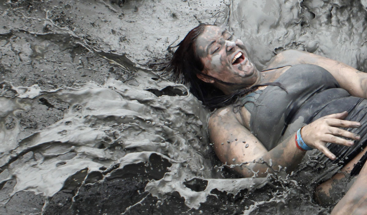 A tourist plays with mud during the opening day of the Boryeong Mud Festival at Daecheon beach in Boryeong, about 190 km (118 miles) southwest of Seoul, July 14, 2012. About 2 to 3 million domestic and international tourists visit the beach during the annual festival, according to the festival organisation.  REUTERS/Lee Jae-Won (SOUTH KOREA - Tags: SOCIETY TRAVEL) ORG XMIT: BOR04