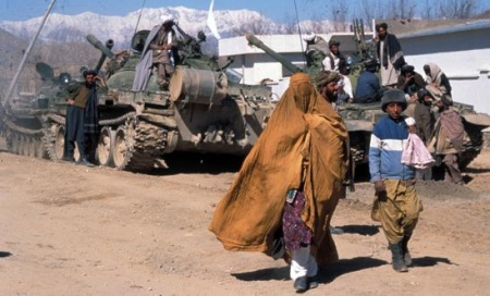 548x331_afghan_woman_and_boy_walk_in_front_of_tank_2004