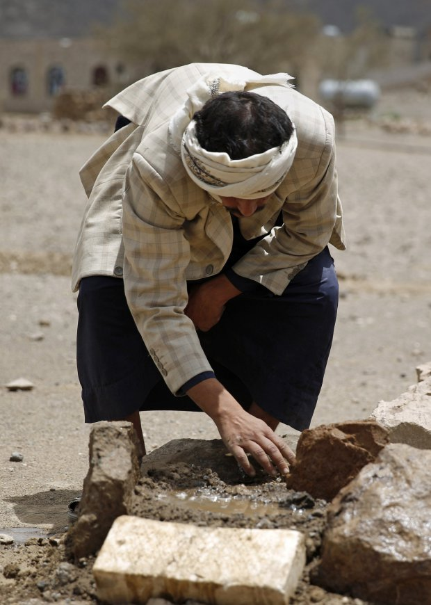 In this Monday, March 28, 2016 photo, Faisal Ahmed, whose son, Udai Faisal, died of severe acute malnutrition, tends to his grave in Hazyaz village, on the southern outskirts of Sanaa, Yemen. Hunger has been the most horrific consequence of Yemenís conflict and has spiraled since Saudi Arabia and its allies, backed by the U.S., launched a campaign of airstrikes and a naval blockade a year ago. (AP Photo/Hani Mohammed)