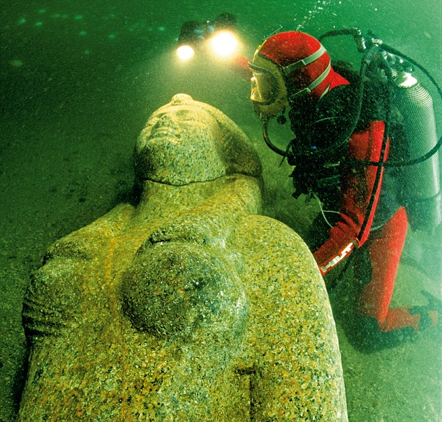Buzo inspeccionando una estatua en el fondo del mar