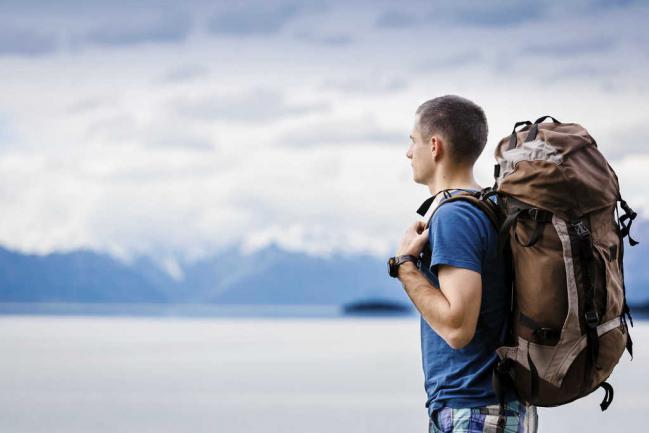 Hombre mirando el horizonte con una mochila de viajes