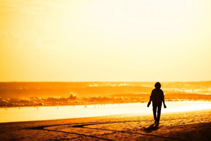 Persona caminando a la puesta de sol