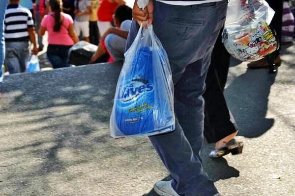 Hombre lleva detergente en una bolsa