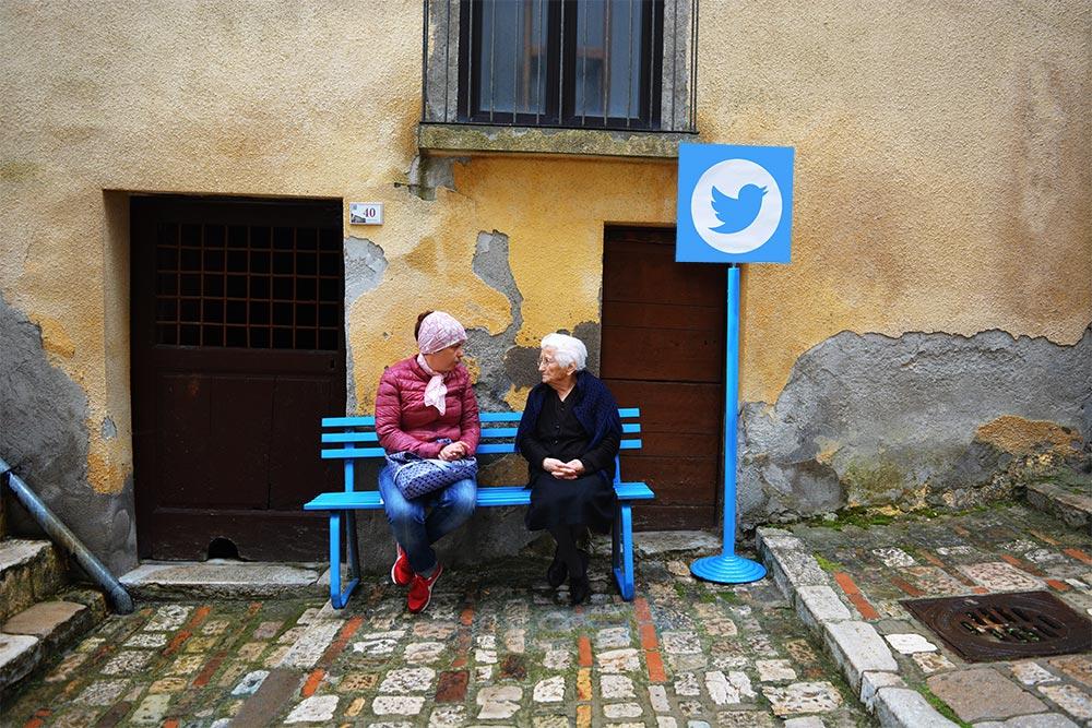 Dos mujeres conversan al lado del logo de Twitter