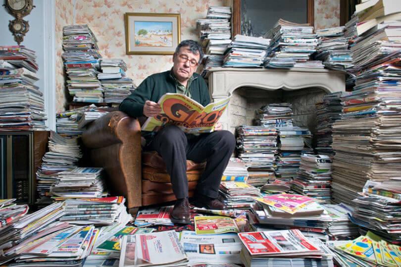 Hombre leyendo periódicos y revistas