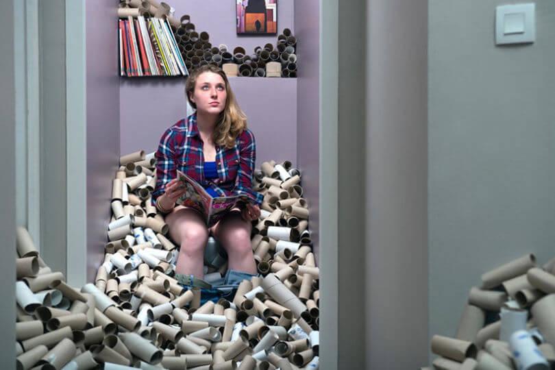 Mujer en un baño lleno de rollos de papel higiénico