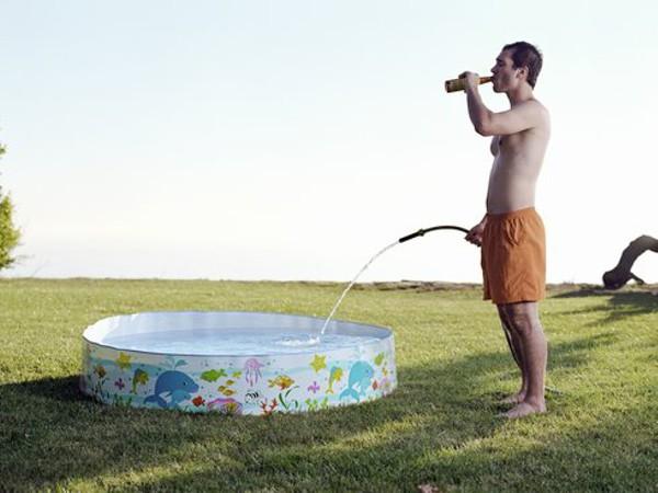 Hombre bebe cerveza y llena de agua una piscina