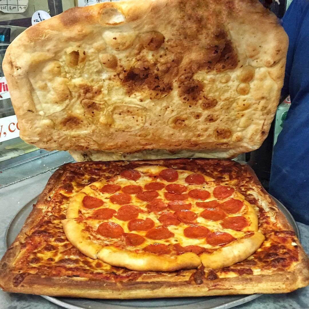 Pizza dentro de la caja de pizza con la tapa abierta