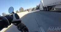 El espeluznante momento en que un motociclista pierde el control y cae debajo de un camión